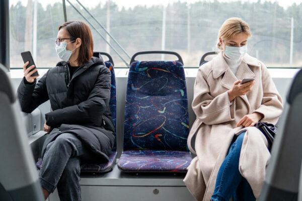 Persoane cu mască chirurgicală călătorind în mijloc de transport în comun.