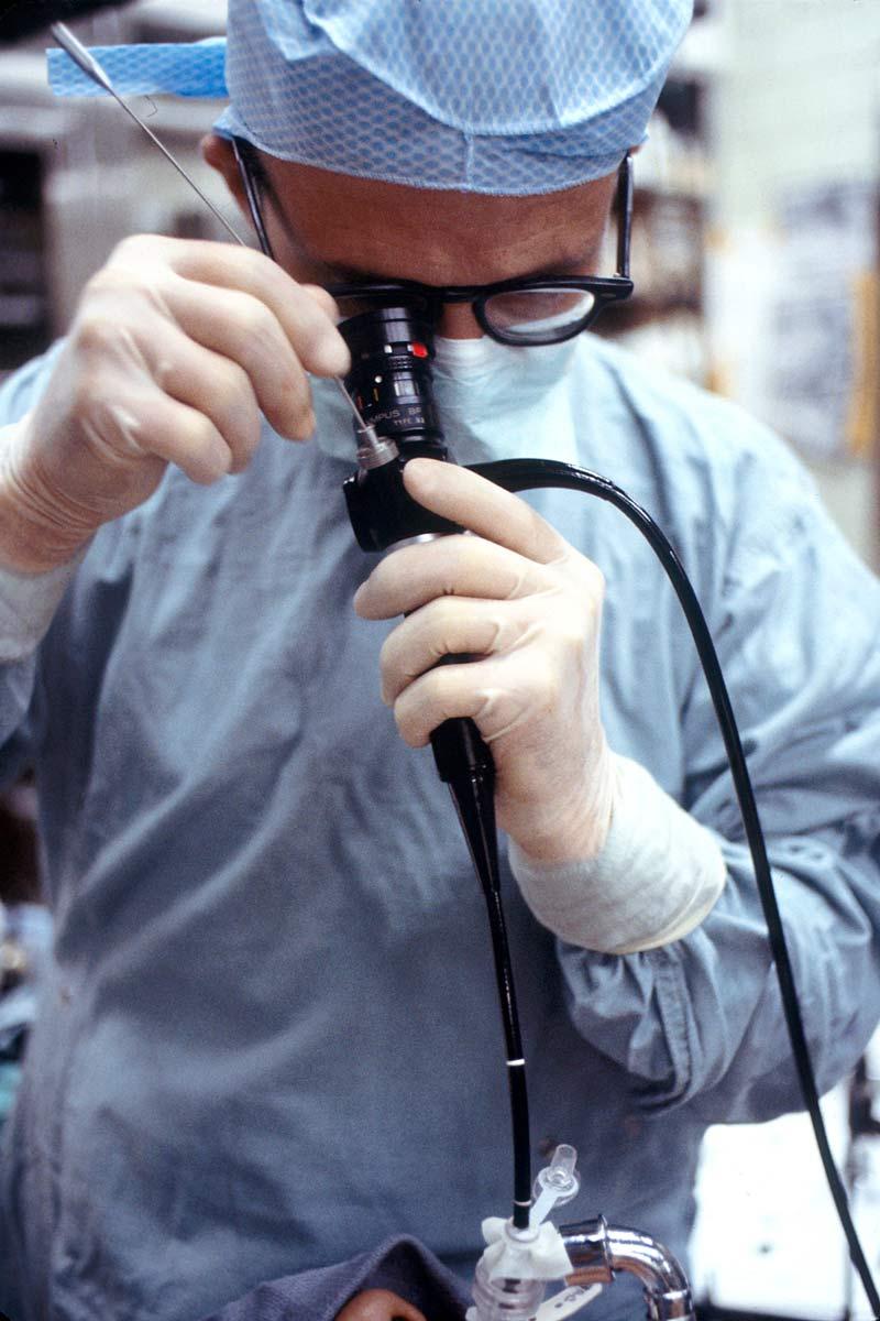 Doctor în echipament de protecție realizând o bronhoscopie.
