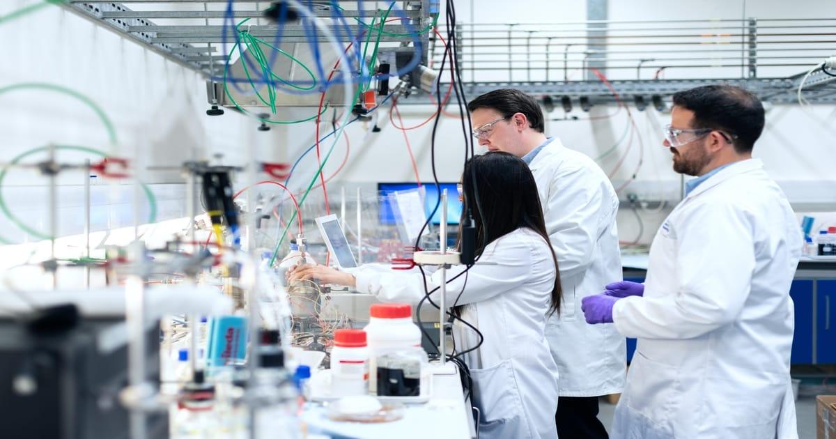 trei cercetatori într-un laborator